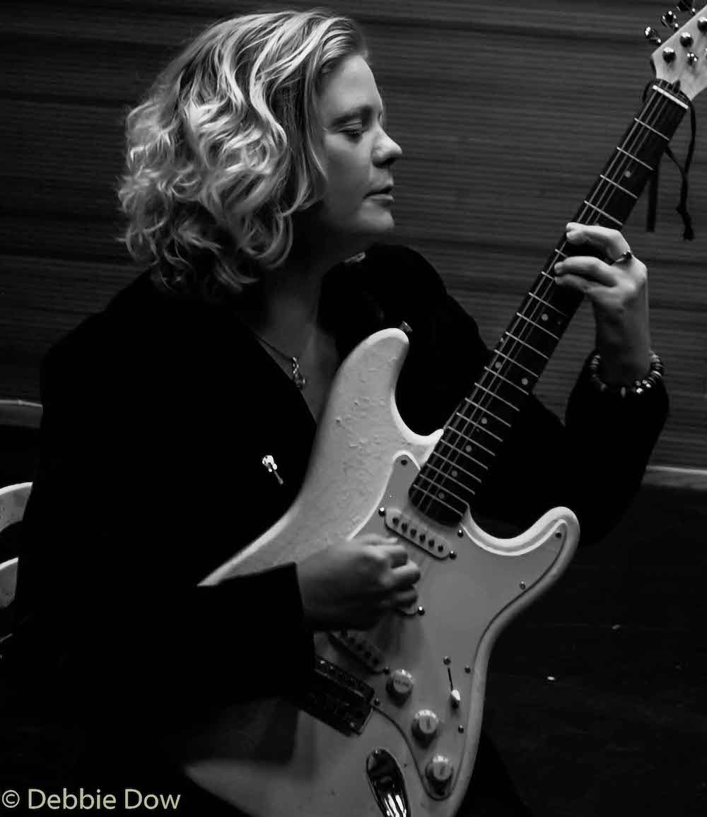Kirsty with her guitar in black and white