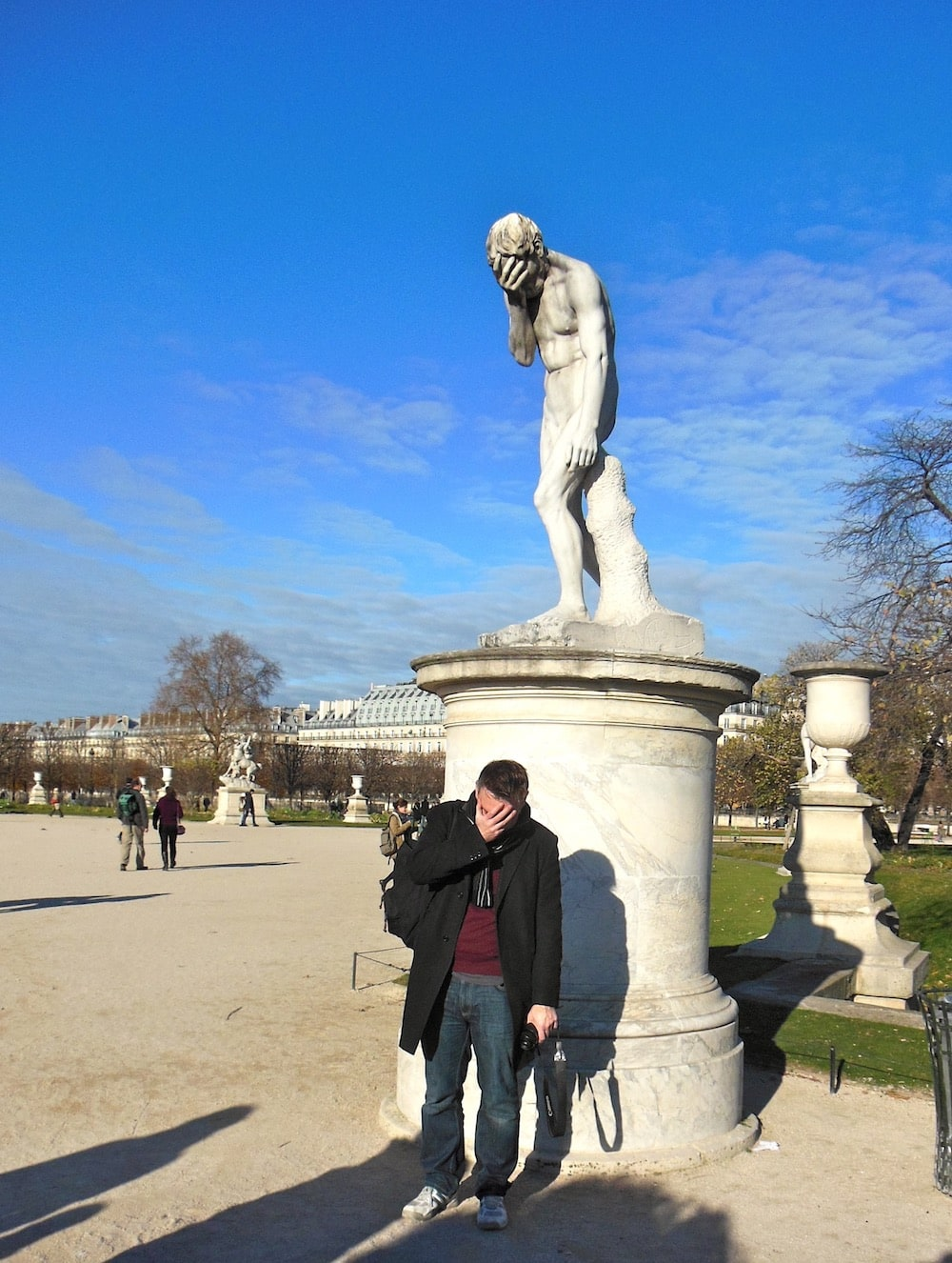 Phil with a statue making a similar pose of his head in his hands