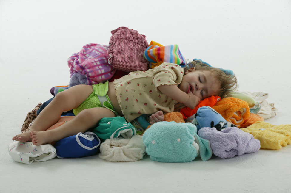 A baby sitting on a pile of disposable nappies