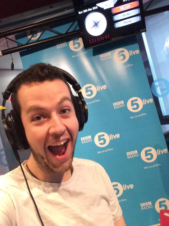 This is photo of Dave psmiling excited behind the scenes of a radio show