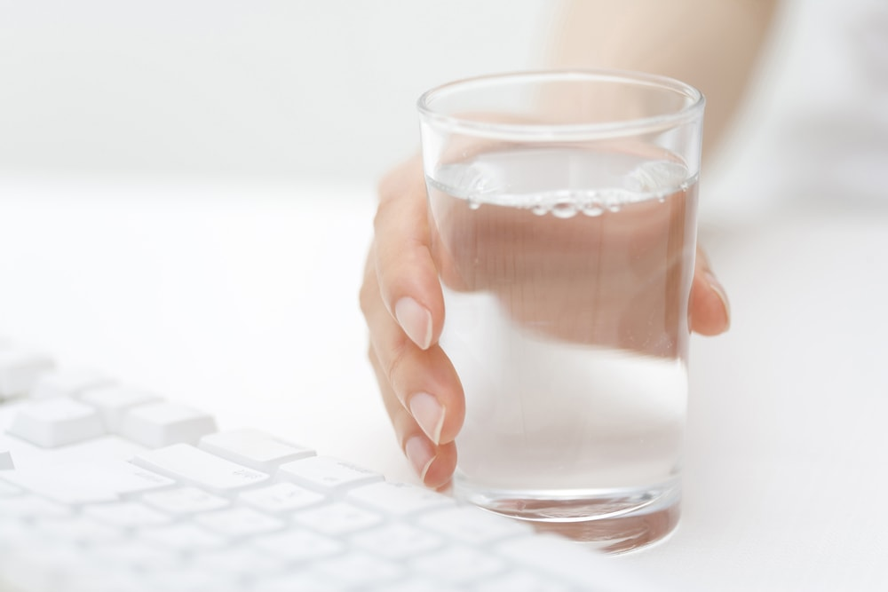 This is a photo of a ladies hand holding a glass of water beside her keyboard