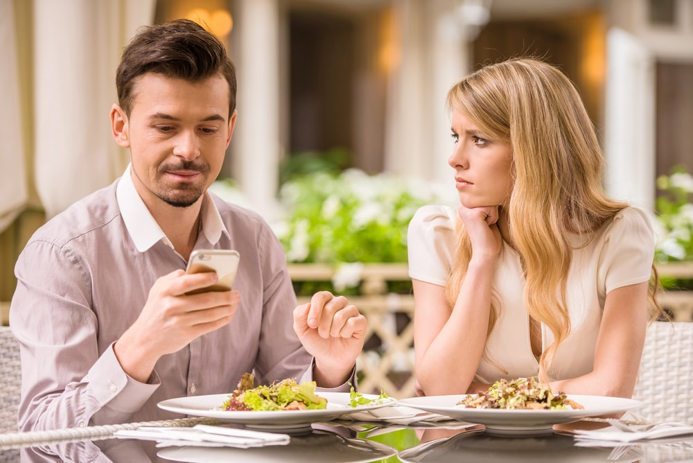 This is a photo of a couple at a restaurant. The man is on his phone, and the woman with him looks unhappily over to him