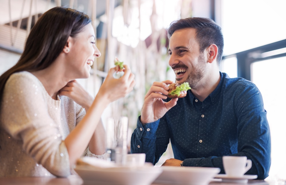 This is a photo of a happy couple at a restaurant. They are both laughing mid-conversation, holding sandwiches