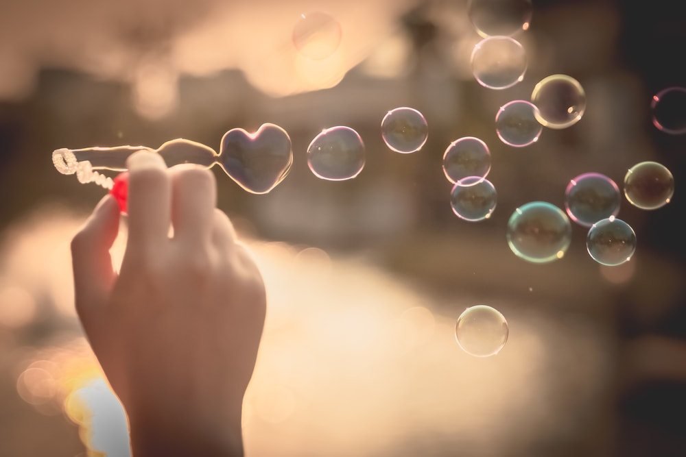 This is a photo of bubbles being blown, with the first in the shape of a heart.