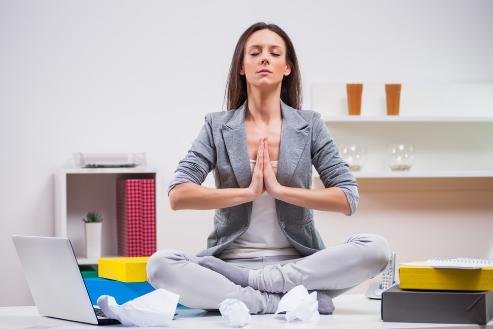 This is a photo of a woman sitting cross-legged, seemingly meditating on a desk, surrounded by paper, files and a laptop