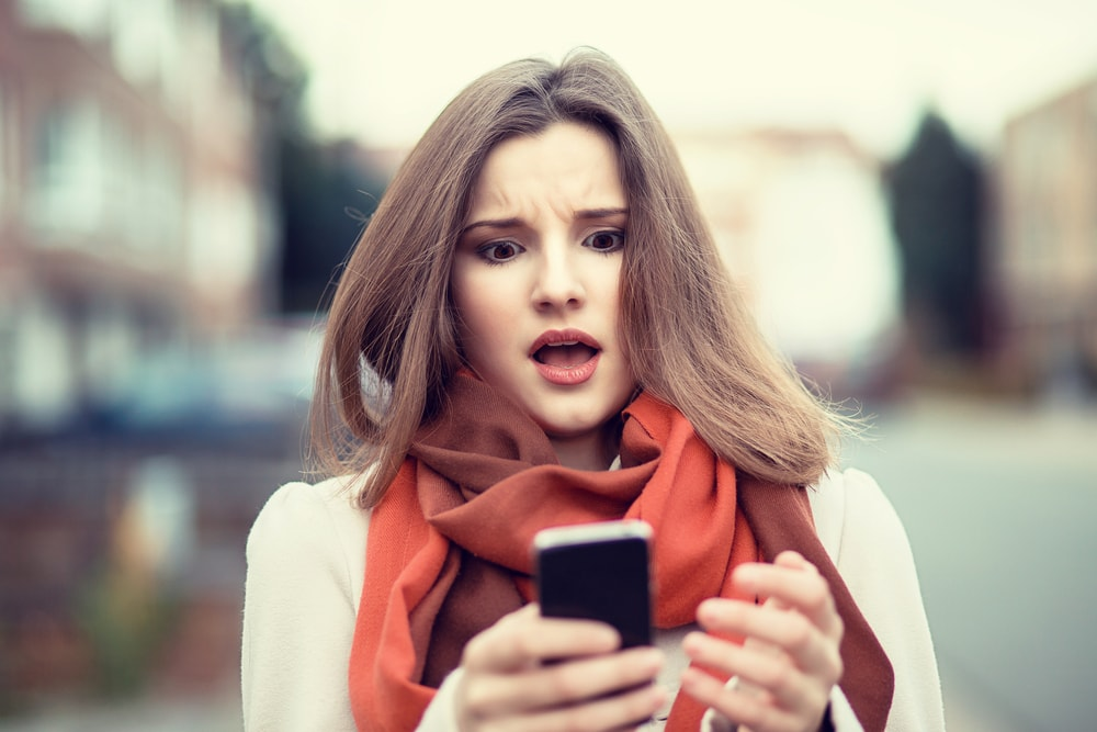 This is a photo of a young woman, looking down in horror at her phone