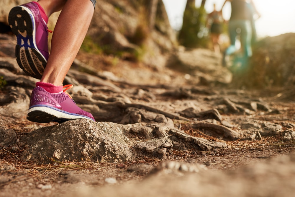 This is a close-up photo of a woman's running shoes as she hikes a rocky trail