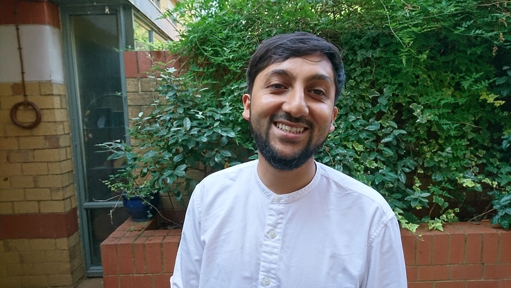 This is a photo of Mohammad smiling with a tree behind him