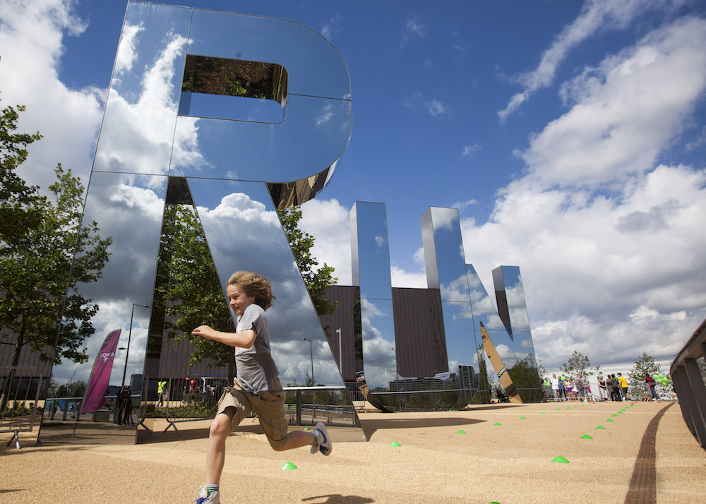This is photo of the a child running past big mirrored 'RUN' letters at the Olympic Park in Stratford, London