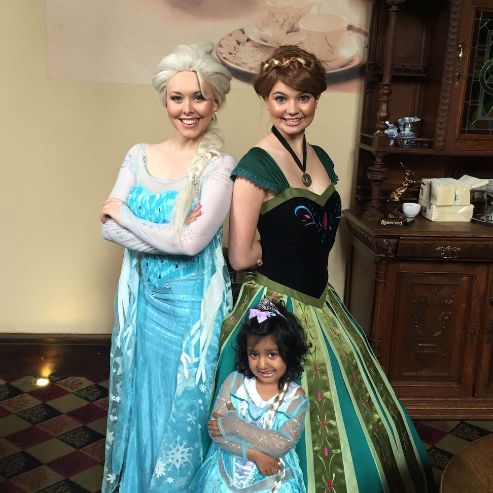 This is a photo of a little girl dressed as a princess with Anna and Elsa from Frozen