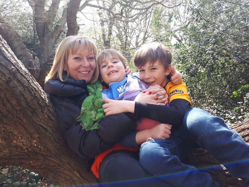 This is photo of Debra sat on a tree branch with her two sons