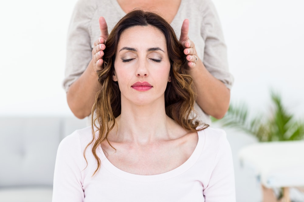 This is photo of a woman sat facing forward with her eyes shut. A therapist is holding her hands just above the woman's hair as she performs the reiki treatment.