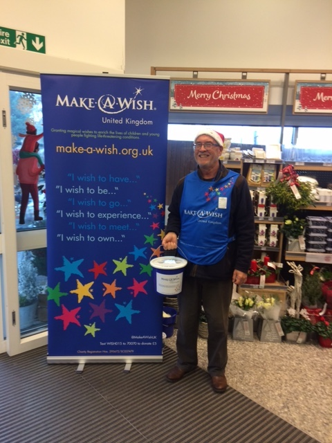 This is a photo of Make-A-Wish volunteer Ray, collecting donations at Waitrose in a Santa hat at Christmas