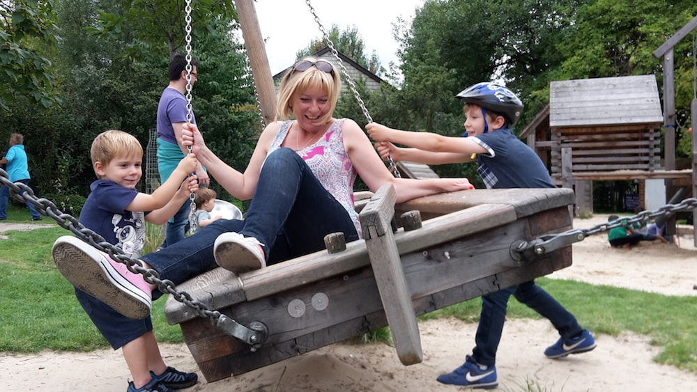 This is photo of Debra playing in a park playground with her sons