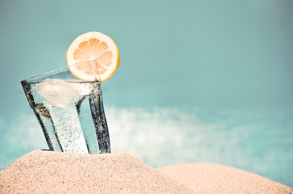 This is a photo of a glass of iced water on the beach