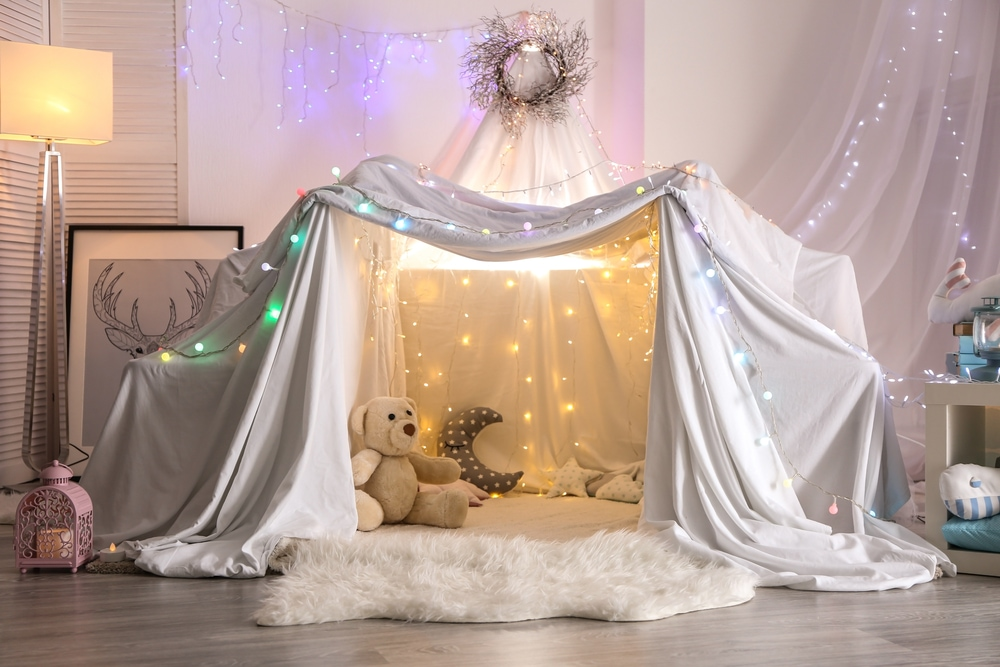 This is photo of a blanket fort with fairy lights and cushions
