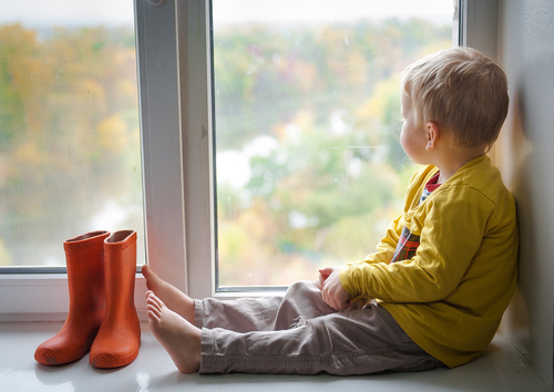 A child looks out of the rainy window