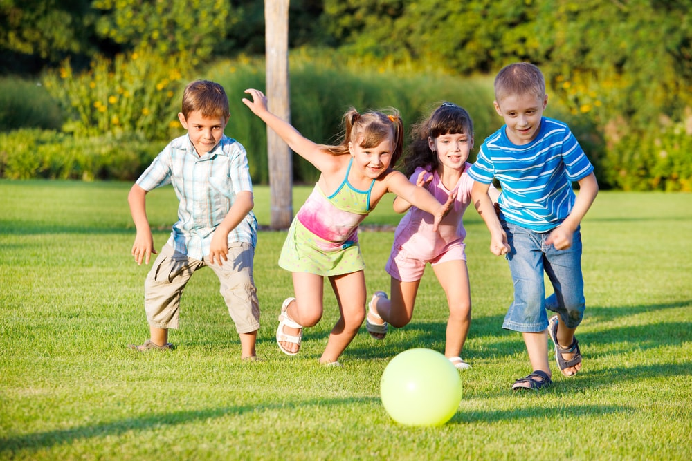 Children chase a ball in the park