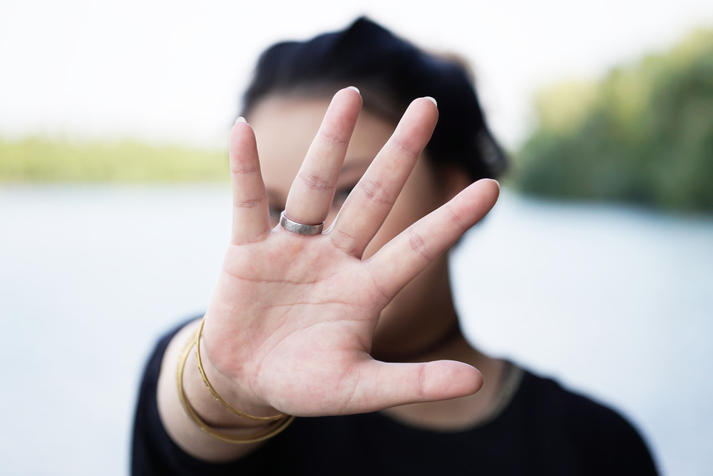 This is a photo of a woman hiding behind her hand