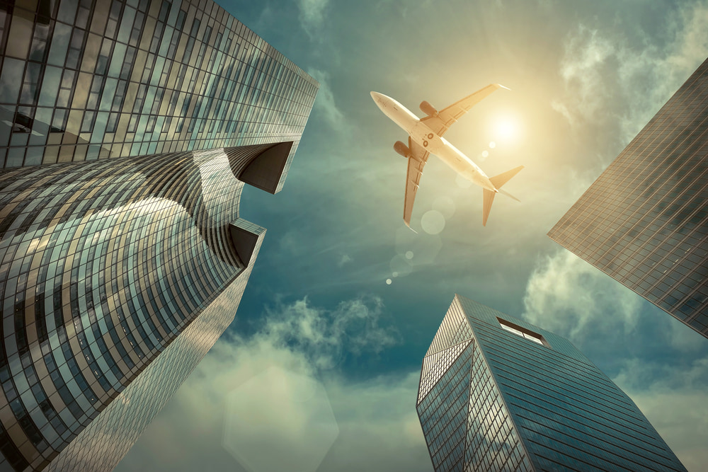 This is a photo of a plane flying over mirrored glass buildings