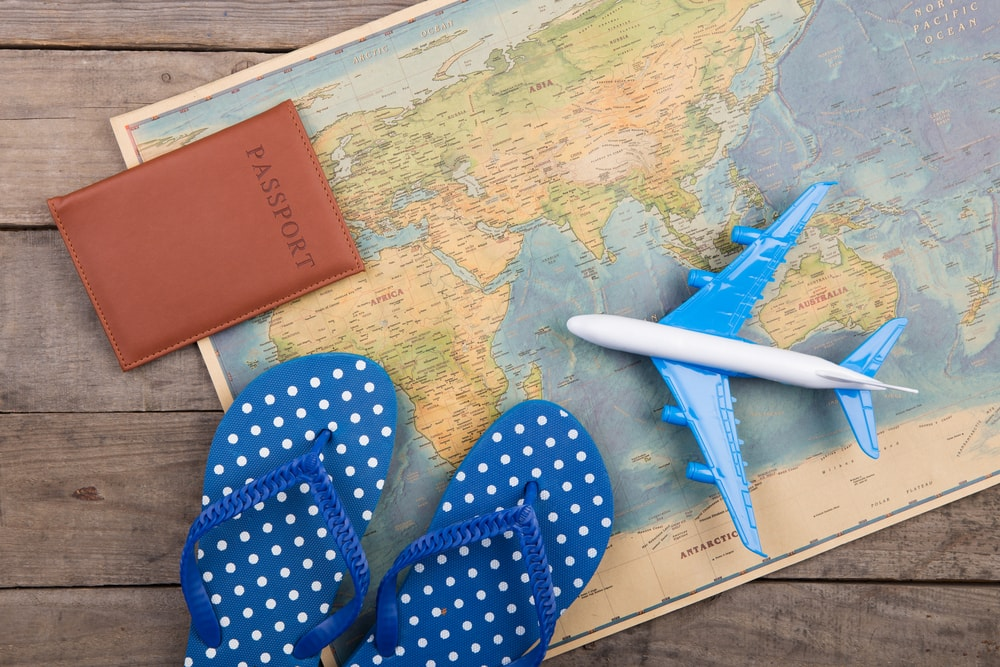 This is a photo of a a map with a passport, flip flops and a mini plane on it