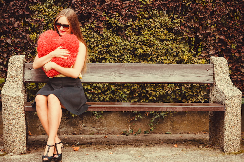 This is a photo of a woman sitting on a bench, holding a heart