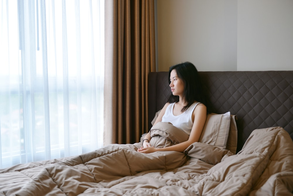 This is a photo of a woman sat in bed, looking unhappy
