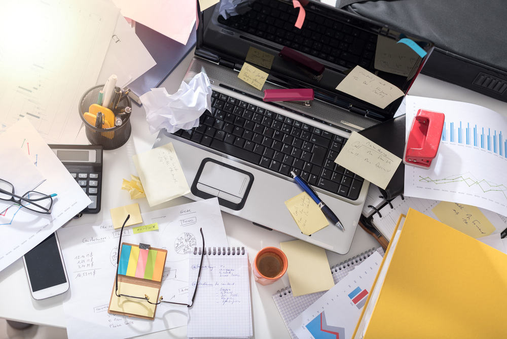 This is a photo of a desk covered in mess and clutter