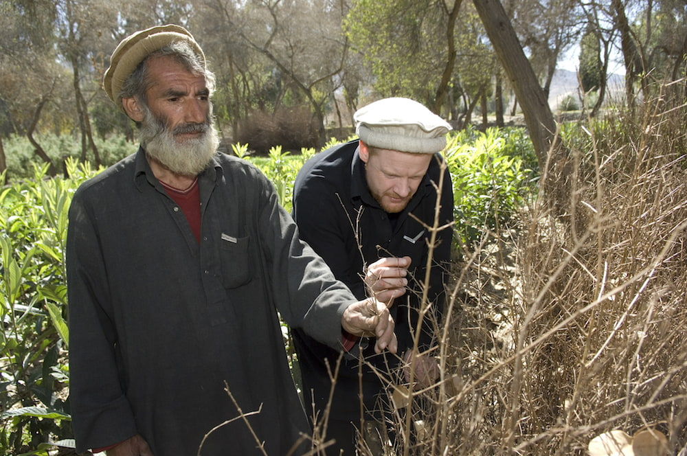 James Brett with a farmer for Plant for Peace
