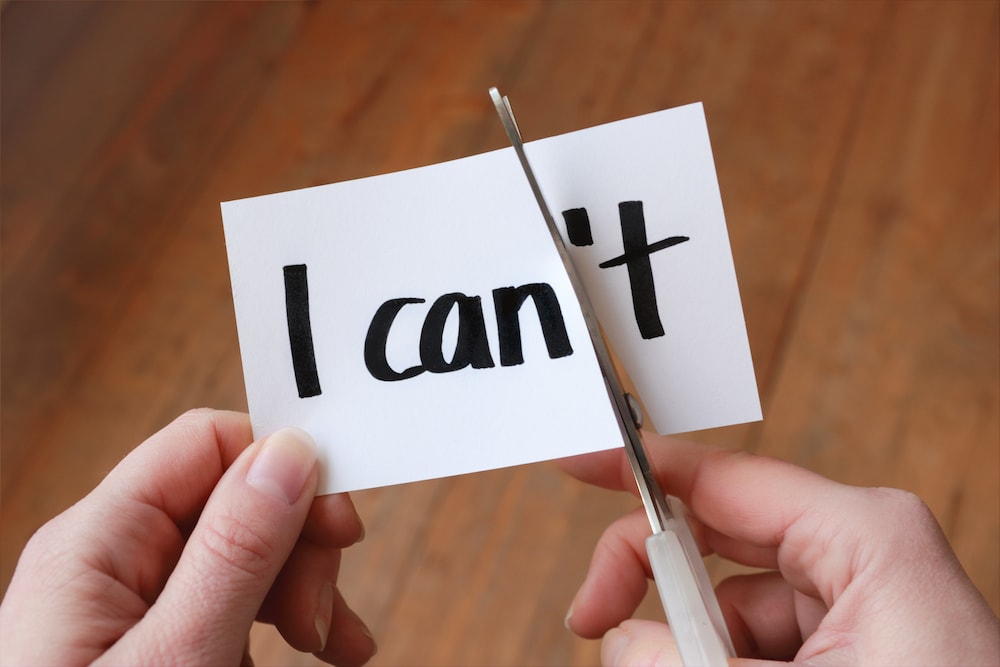 This is a photo of someone cutting the word 'I can't' so it reads 'I can'