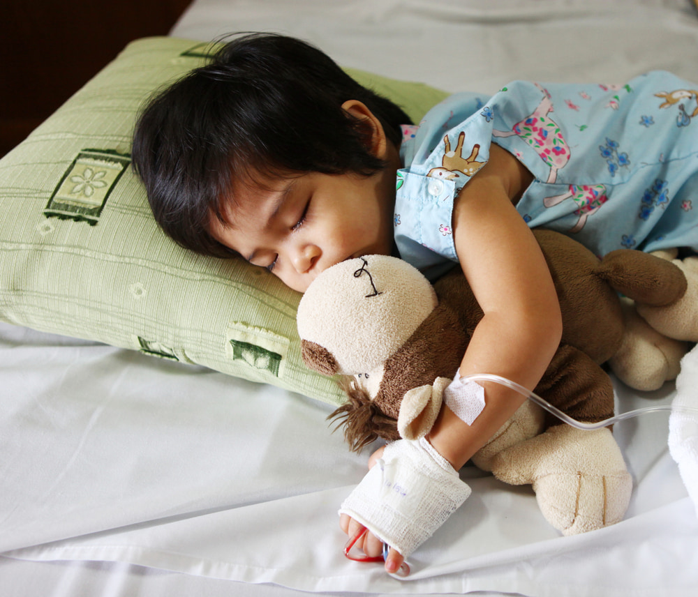 Young child cuddles monkey toy in hospital while sleeping