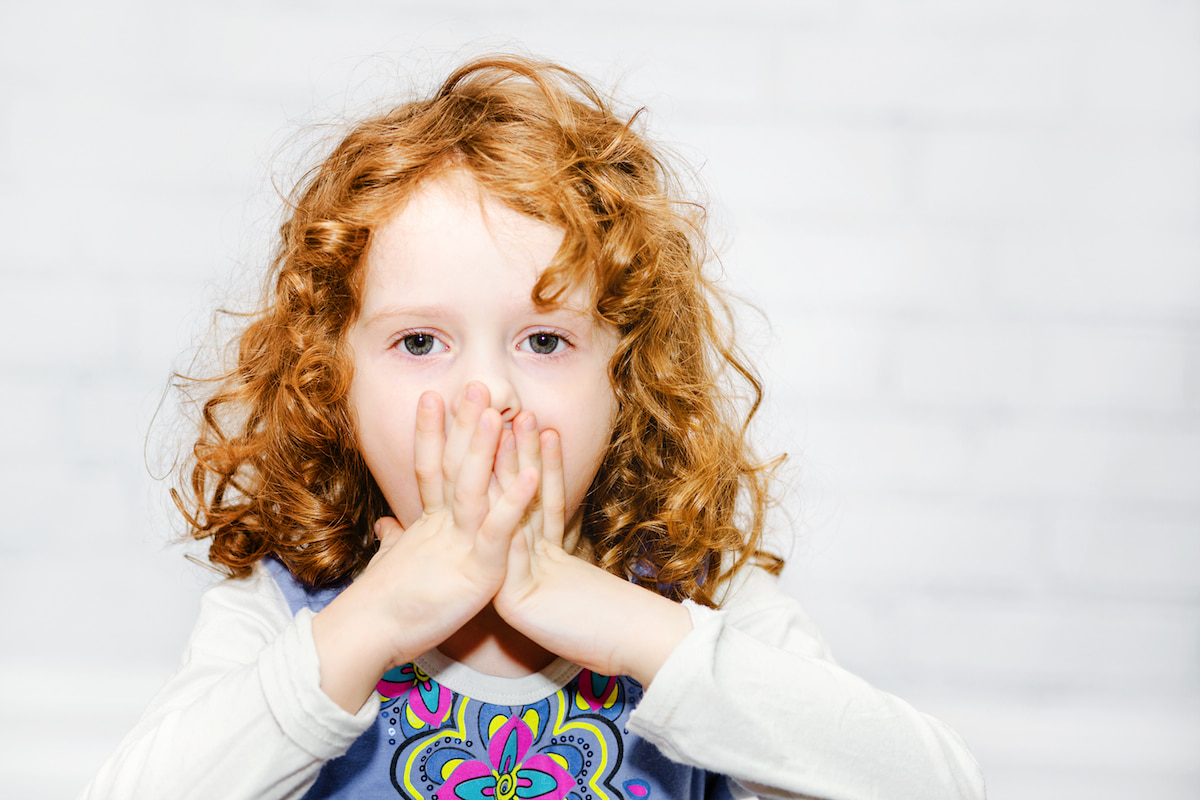 A young red-head child gasping, covering her mouth