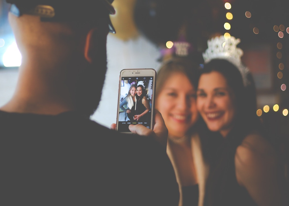 man taking photo of women at party