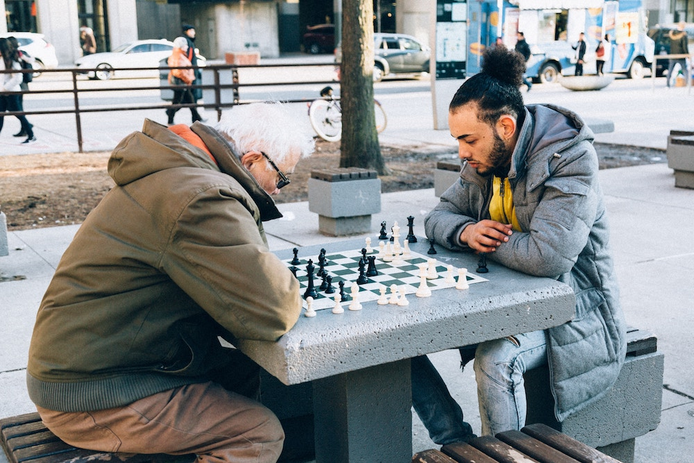 old man and young man playing chess