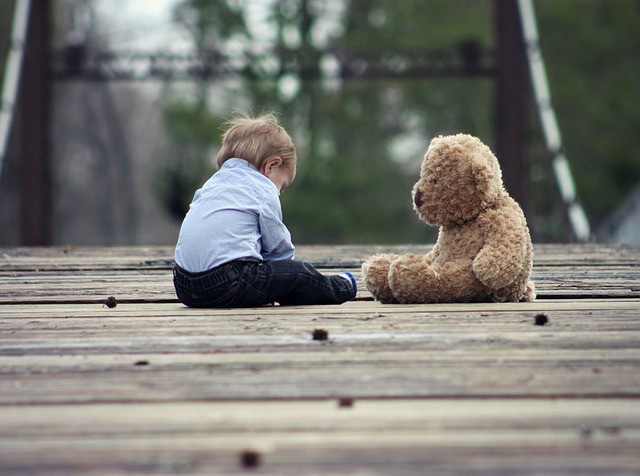child-plays-alone-with-teddy-bear