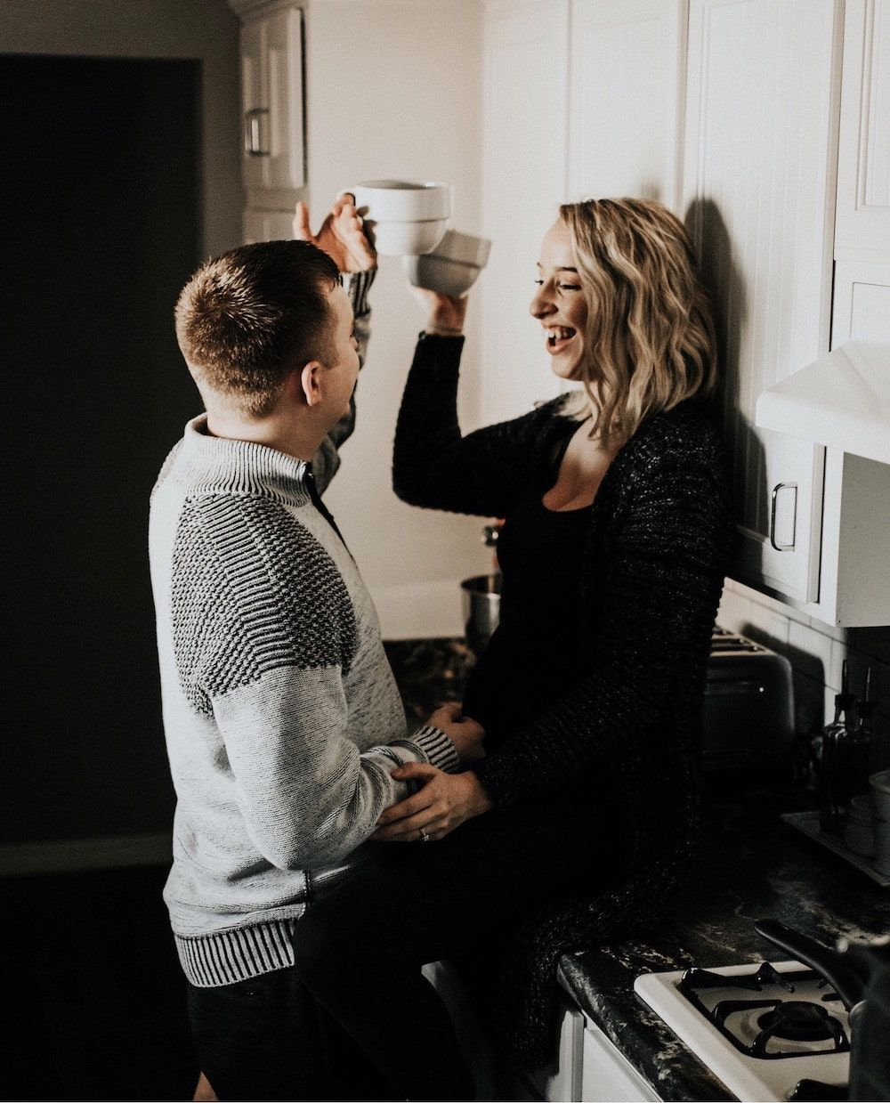 couple celebrating with cup of coffee in kitchen
