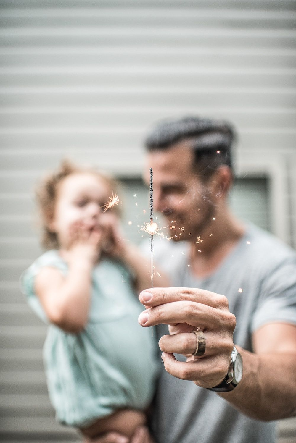 father holding daughter and celebrating with a sparkler