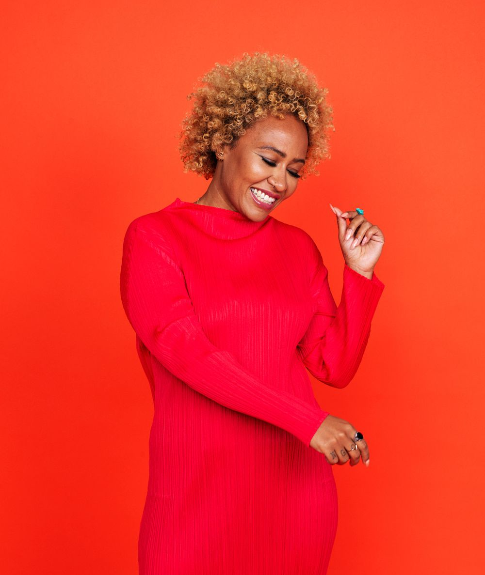Emeli Sande wearing a red dress, smiling and dancing