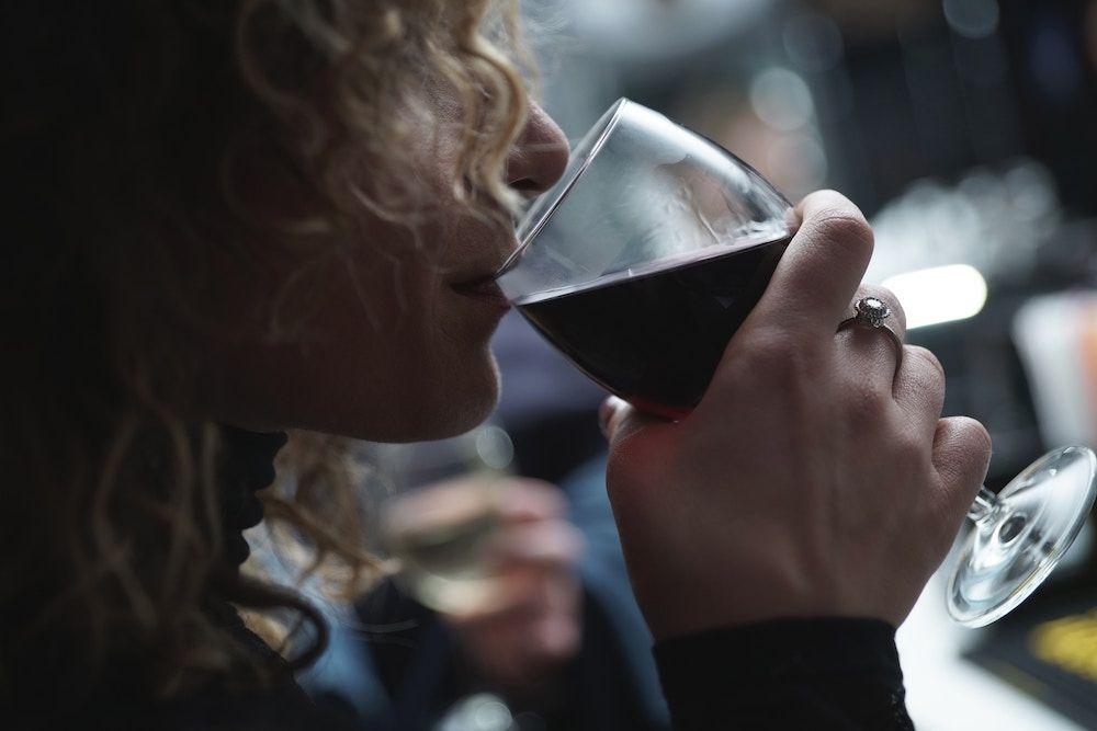woman drinking red wine from a glass