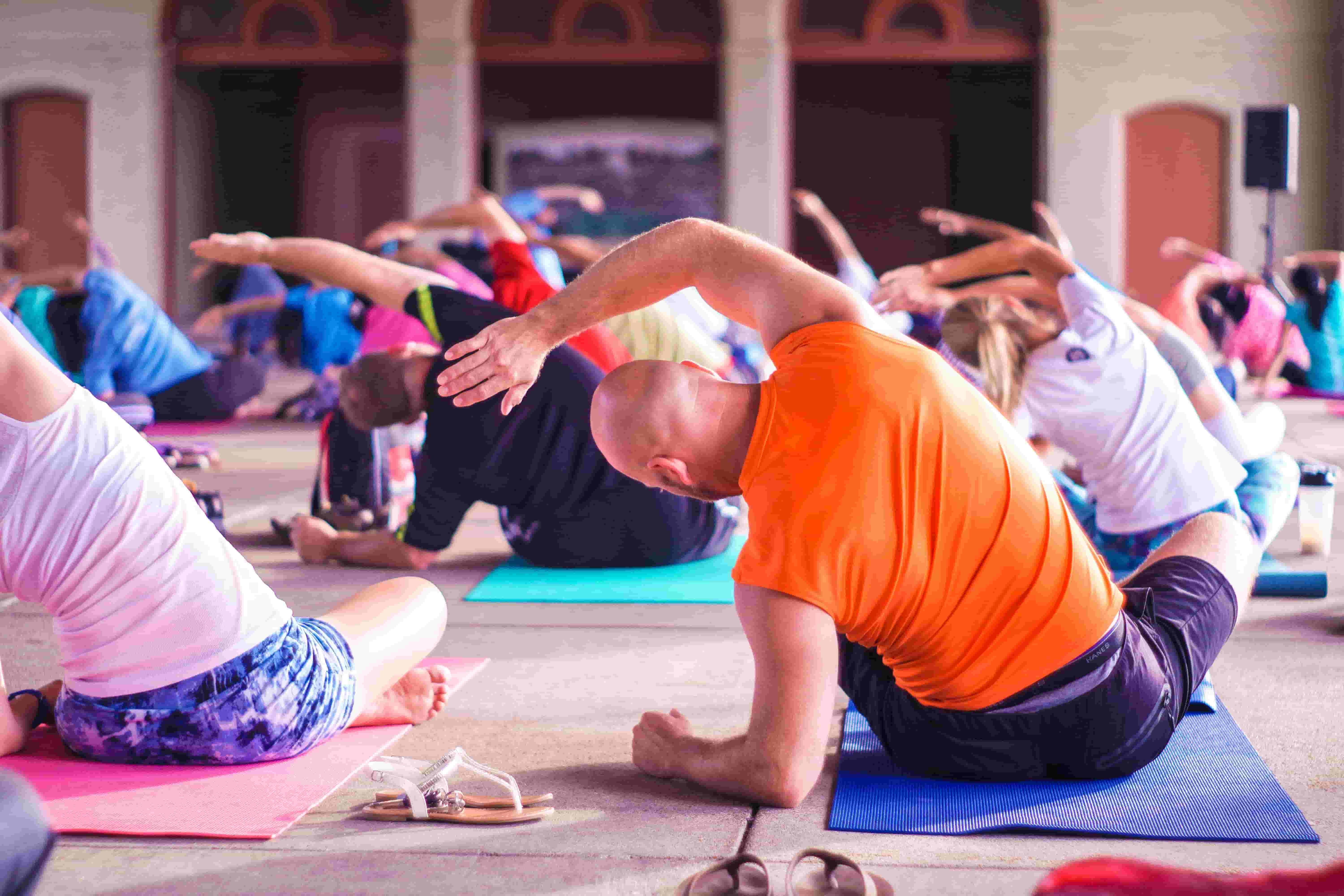 A middle-aged man takes part in a yoga class.