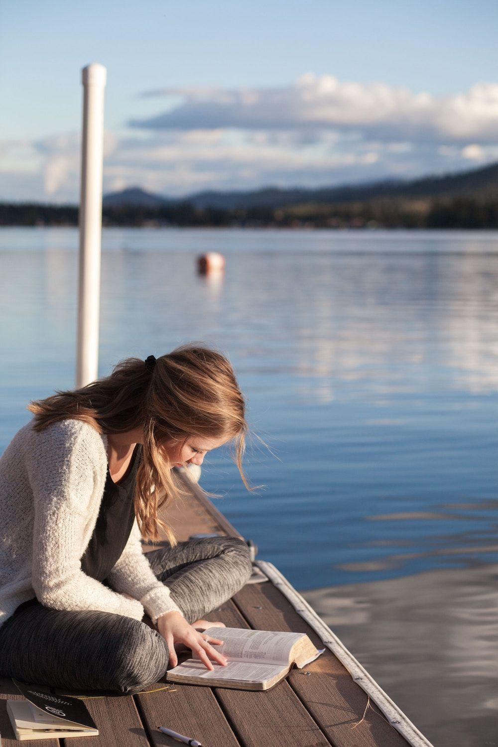 woman sitting outside by a lake reading a book