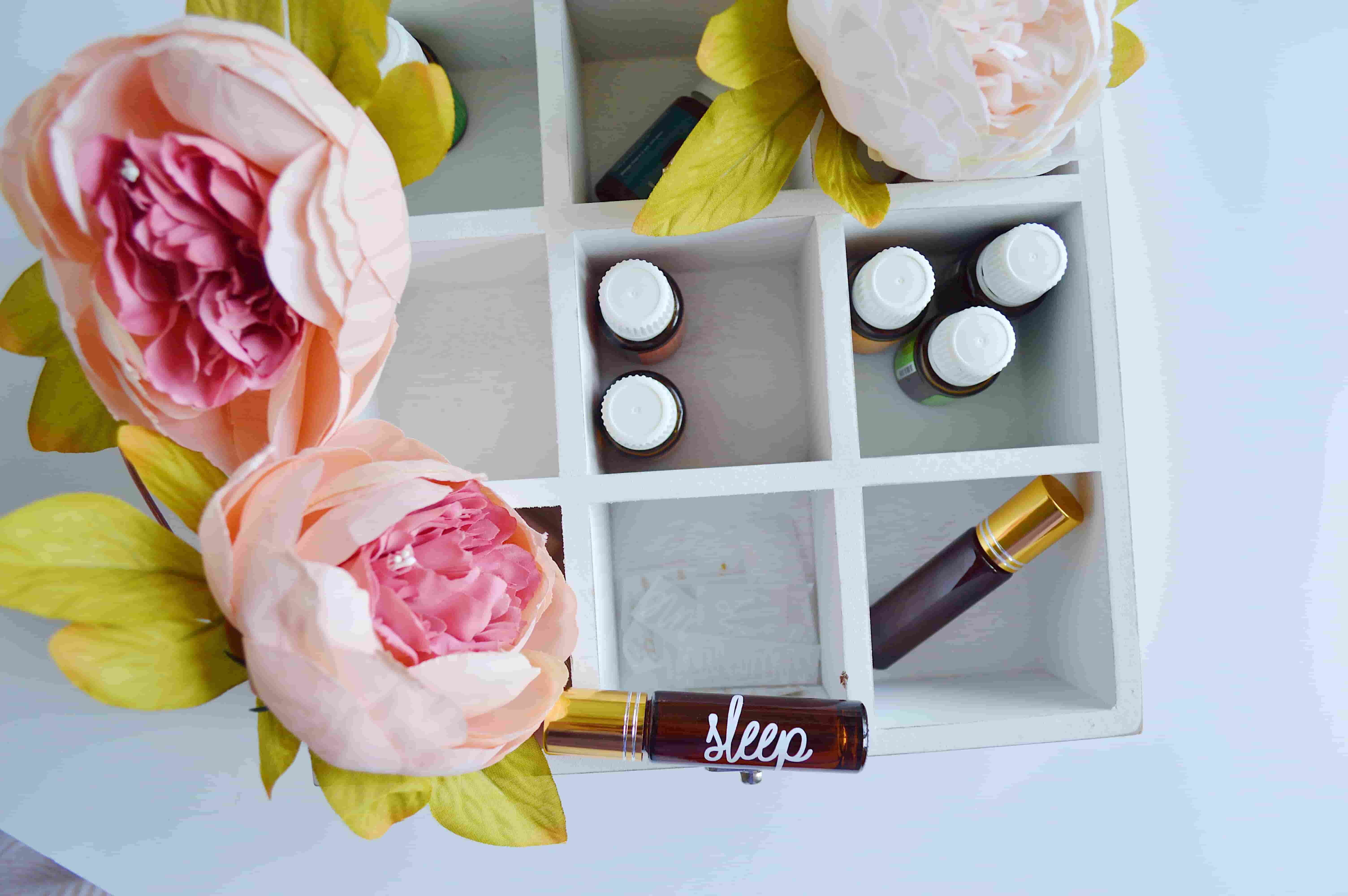 A white painted box has natural pink blossoms resting against it. Within the box, aromatherapy oils labelled with scents and the word 'sleep' are resting.