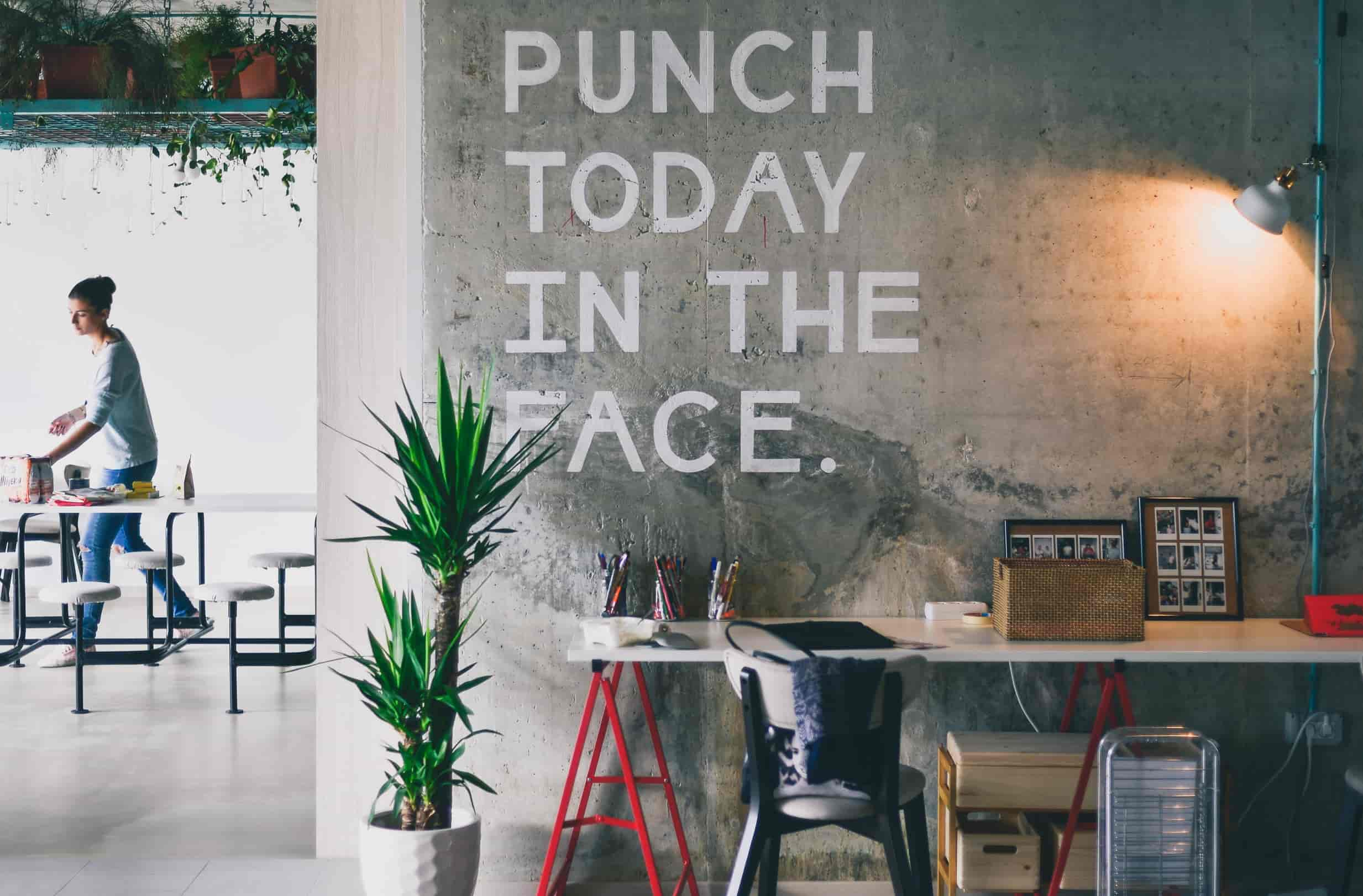 A motivational quote is written on a bare concrete wall in a modern office. It says: punch today in the face.