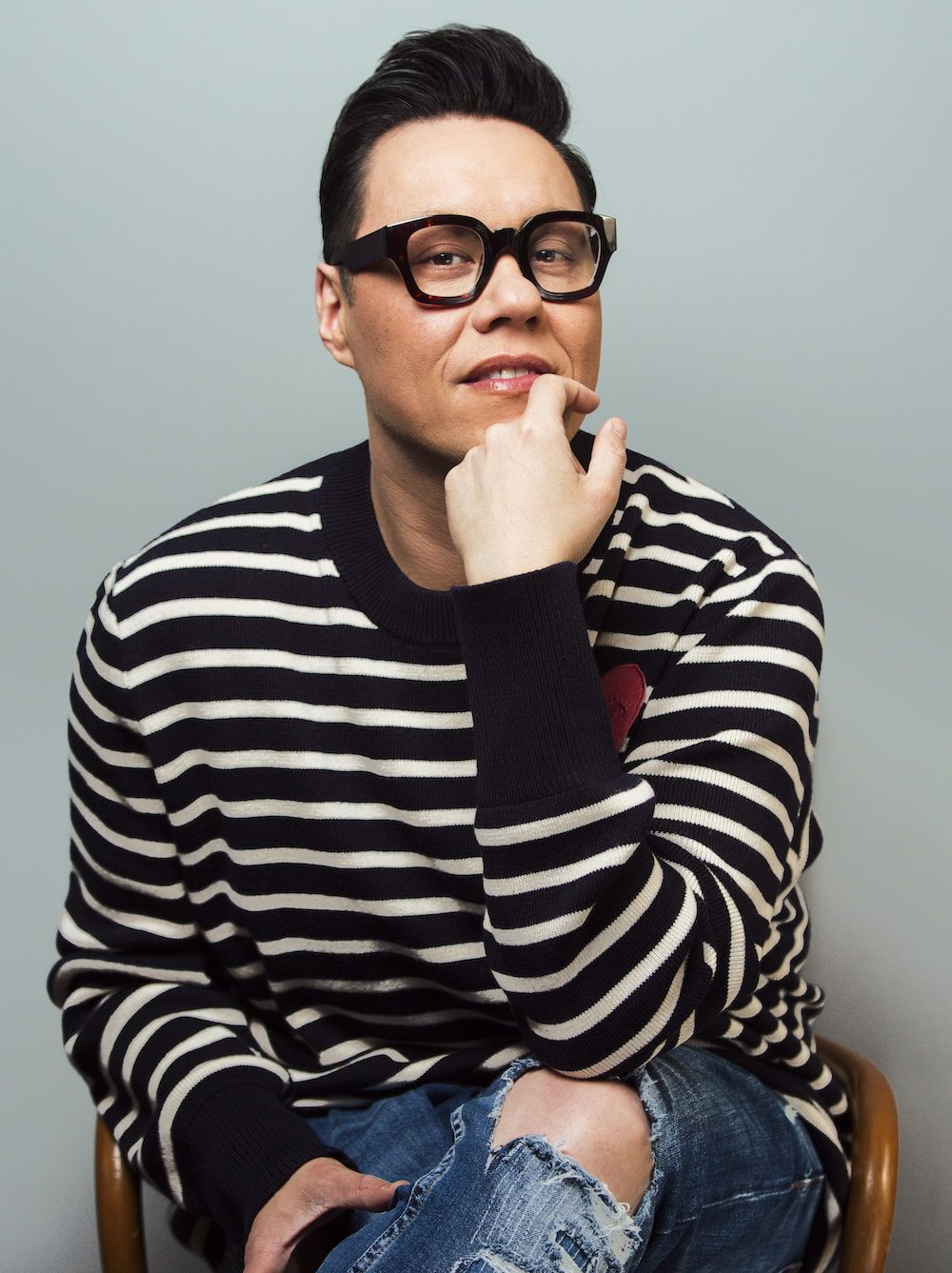 Gok Wan sitting in a chair with his chin resting on his hand