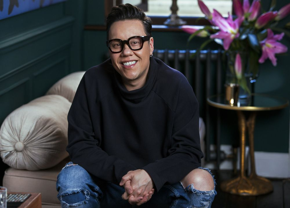 Gok Wan smiling at the camera, wearing a black roll neck jumper and ripped jeans