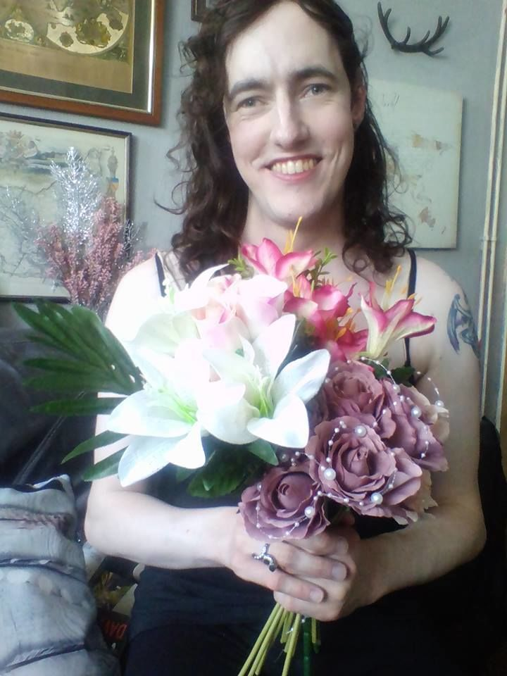 Morgana holding a bouquetof flowers and smiling