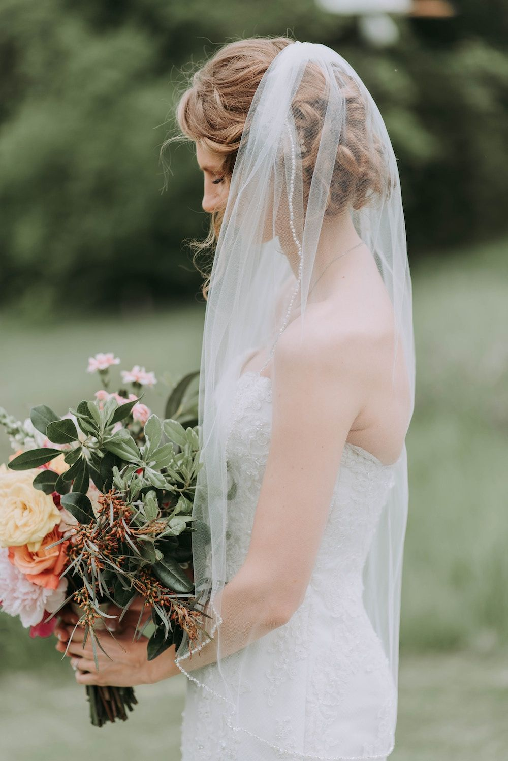 bride wearing veil and holding bouquet