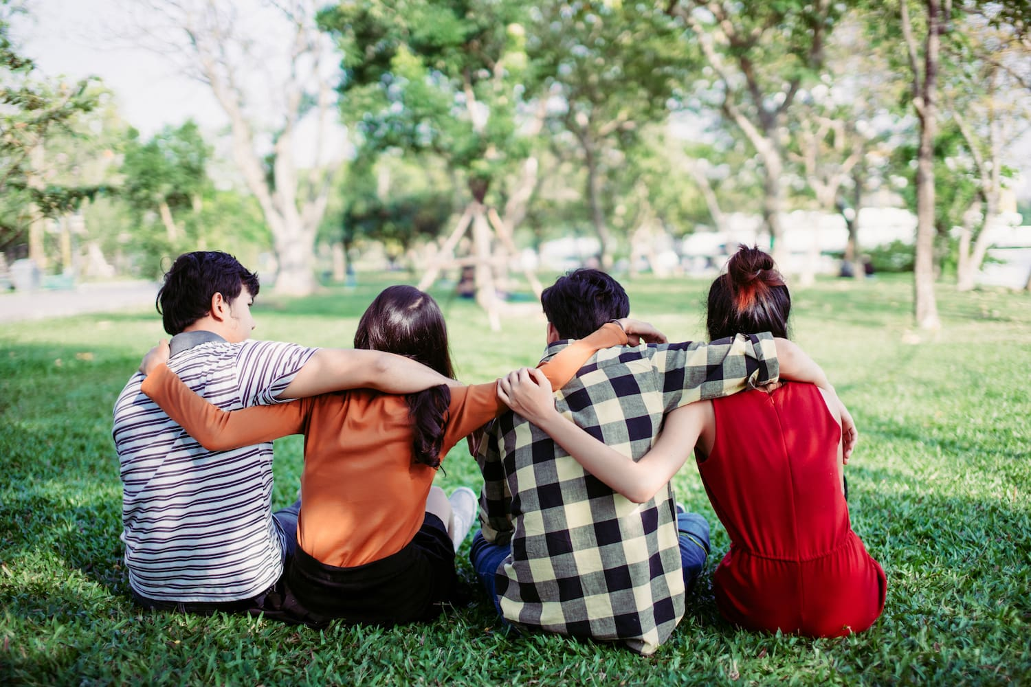 Four friends sat with their arms around each other