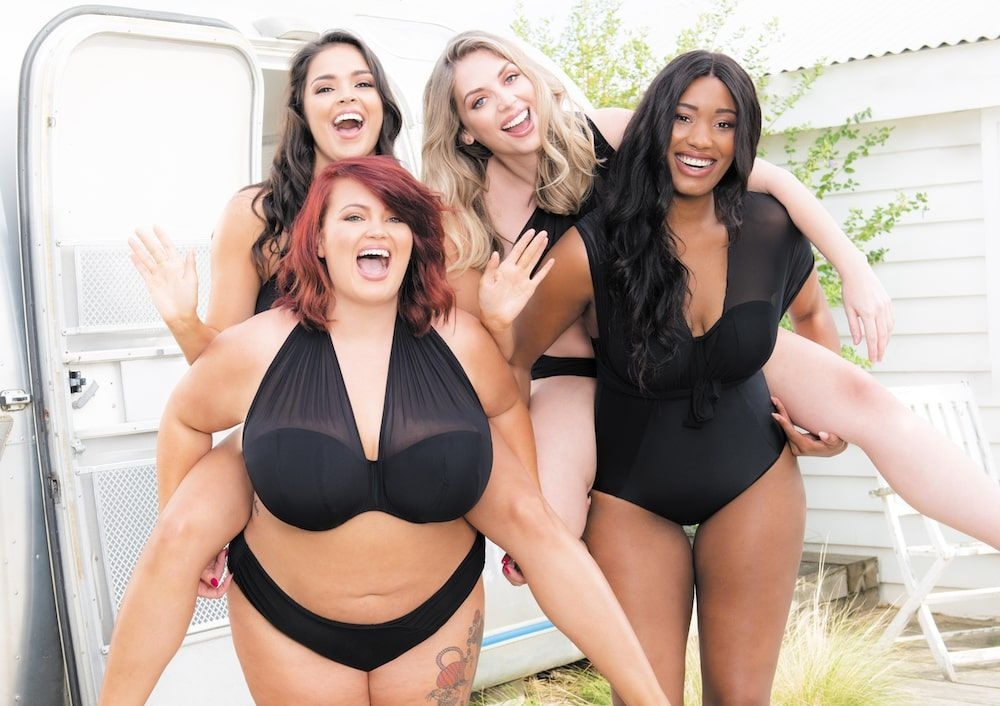 Georgina Horne laughing with a group of models on set at a lingerie photoshoot
