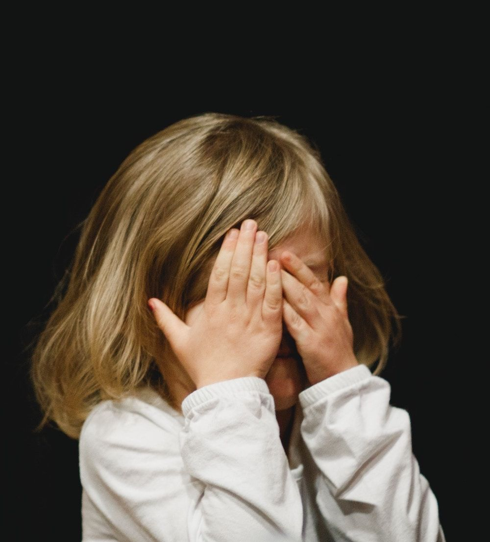 small child covering eyes